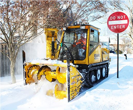 Skid loader plowing snow